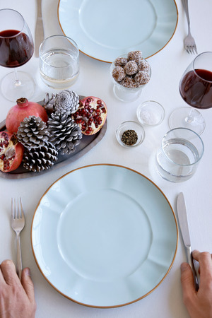 Hands at a dinner table with wine and crockery, decorated with pine cones, pomegranate for the festive holidays christmas photo