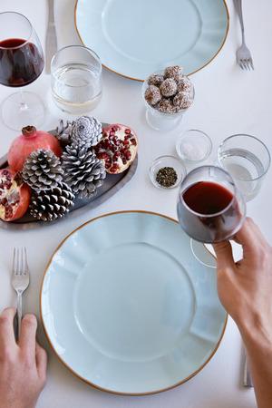 瀬戸物: Hands at a dinner table with wine and crockery, decorated with pine cones, pomegranate for the festive holidays christmas