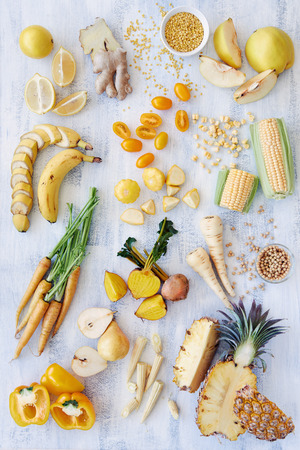 Assorted fresh raw organic produce in yellow hues, pepper capsicum carrot pineapple corn banana parsnip pear soya beans lentils quince, part of a color spectrum collection see more in my portfolio photo
