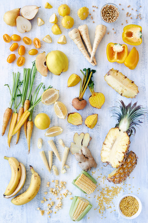 fresh produce: A selection of various fresh yellow raw organic produce fruits and vegetables pineapple carrot parsnip capsicum soy beans lemon tomato pear corn banana beetroot - part of a color spectrum collection see more in my portfolio Stock Photo