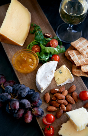 Cheese tasting platter with hard, soft, white rind assorted cheese, jam, grapes, raw almonds, cherry tomatoes, crackers and wine, perfect party entertaining gourmet food photo