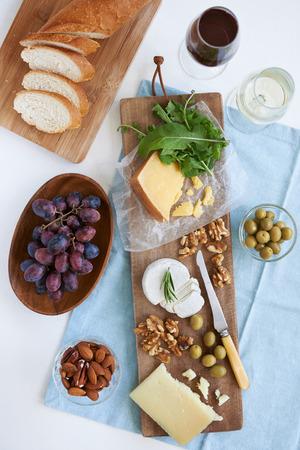 Cheese platter starter appetiser pre dinner snack, assortment of different cheeses, nuts, olives and grapes served with wine photo