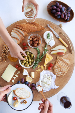 Hands reaching for food on a well spread cheese platter, party snack appetiser with wine photo