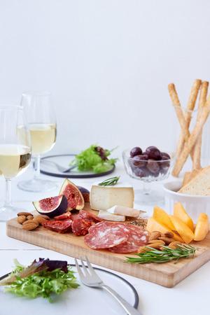 charcuter�a: Primer plano de queso y embutidos emparejamiento, salami chorizo, servido con rockmelon fruta fresca, higo con aceitunas, ensalada y vino blanco con un mont�n de espacio de la copia