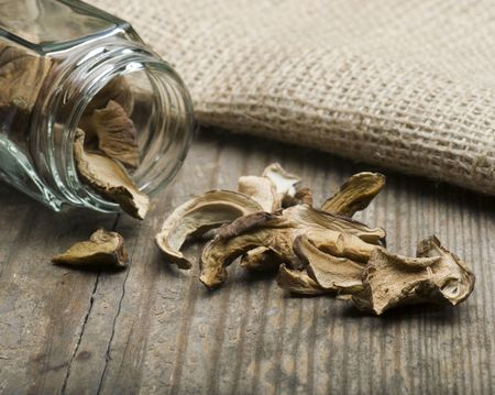 hessian bag: Dried Porcini Mushrooms Spilling Out Of A Jar On To A Wooden Table With A Hessian Bag in The Background