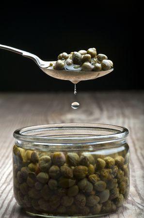 c�pres: Un Spoonful Of Capers Dripping Over A Jar, sur une table de cuisine en bois