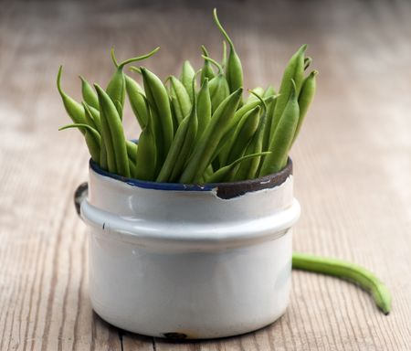 freshly picked: Freshly Picked Green Beans In An Old Enamel Mug On A Wooden Surface Stock Photo
