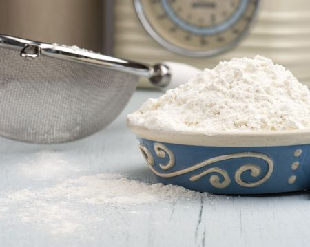 A Dish Full Of Flour With A Sieve and Scales In The Background photo