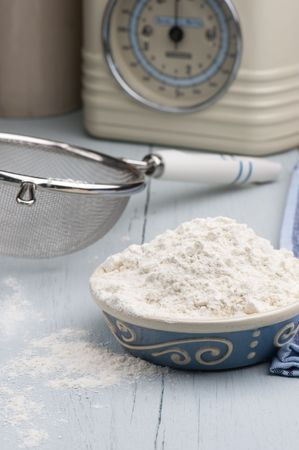 A Dish Full Of Flour With A Sieve and Scales In The Background, On A Wooden Kitchen Table photo