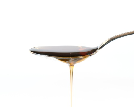 syrup: Maple Syrup Overflowing Off A Silver Dessert Spoon Stock Photo