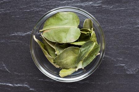 kaffir: A Dish Of Dried Kaffir Lime Leaves, Set Up On A Slate Work Surface Stock Photo