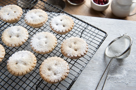 Freshly Baked Mince Pies on a Cooling Rack and Been Sprinkled With Icing Sugar photo