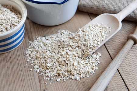 quaker: Porridge Oats, Scoop, Spurtle and Pan on Wooden Kitchen Table Stock Photo
