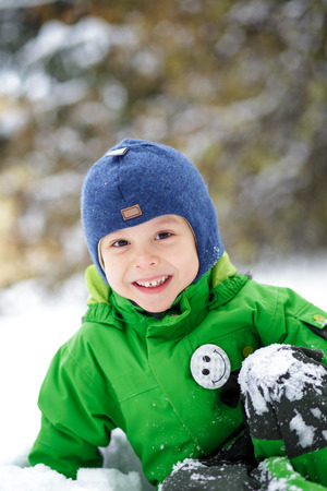 Little smiling boy sitting in the snow