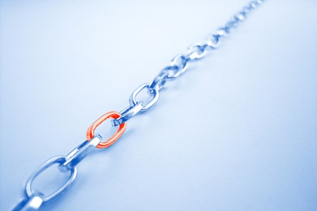 Chrome chain with a red link on blue background
