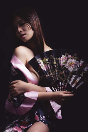 25 30 years women: Asian woman in traditional silk gown holding fan Stock Photo