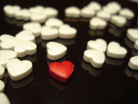 distinguishing: Close-up of a red heart-shaped tablet among the white ones on the dark glossy surface