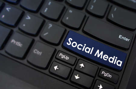 unrecognisable person: Social media on laptop keyboard