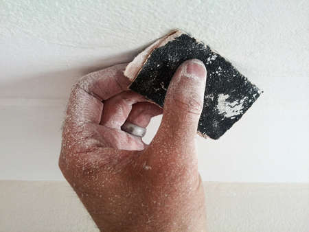 sandpaper: dusty Do it yourself hand holding sandpaper
