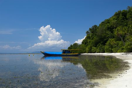 Tropical beach on the Togians Islands (Indonesia) - a fishing boat can be seen in the background. Stock Photo