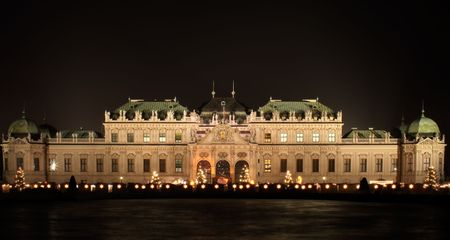 A nightshot of the Belvedere Palace in Vienna. In front of the palace the decorations of a Christmas Market can be seen. The photo was composed from multiple shots with different exposure times (DRI).