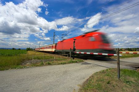 Train passing through a railway crossing against a blue sky with an interesting cloudscape. Motion blur is used to show the movement of the train. Stock Photo