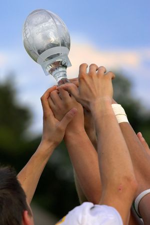 team victory: Hands reaching for a trophy after winning the championship game. Stock Photo
