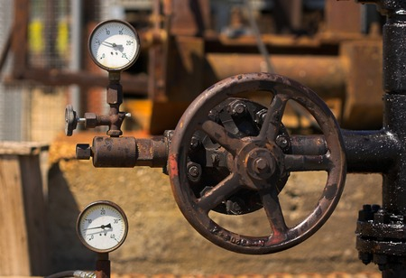 Old machinery - a big valve handle and two gauges are shown. Stock Photo