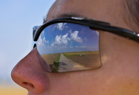 Portrait with sunglasses - the reflexion in the glasses show a nice blue sky with clouds. Stock Photo
