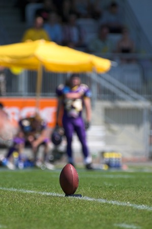 punt: A football in its holder - in the background player and part of the stadium can be seen.