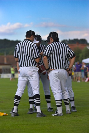 penalty flag: Team of football referees discussing their decision. A penalty marker can be seen on the ground.