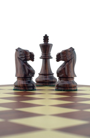 Chess pieces - two black knights guarding the king Stock Photo