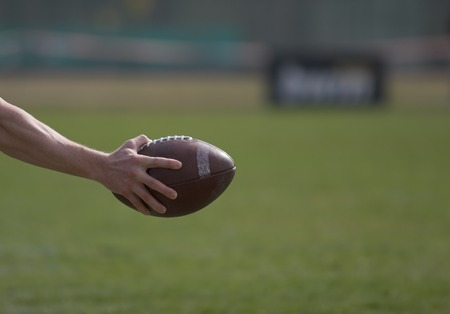 punting: Football - a hand holding a footbal reaches into the picture.