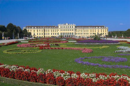 View of Schloss Schoenbrunn in Vienna, Austria against a clear blue sky.