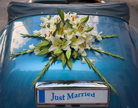 Flower bouquet used as a weeding decoration on a car. The number plate can be used for a message.