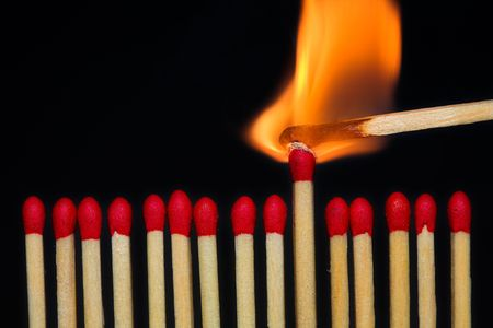 A row of matches, with one of them burning.