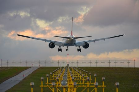 Photo of an airplane just before landing. Runway lights can be seen in the foreground. Stock Photo - 2047508