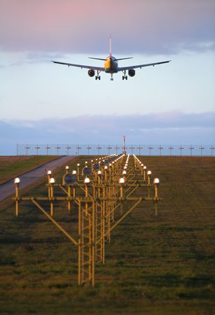 Photo of an airplane just before landing. Runway lights can be seen in the foreground.