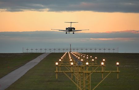 Photo of an airplane just before landing. Runway lights can be seen in the foreground. Stock Photo - 2047510