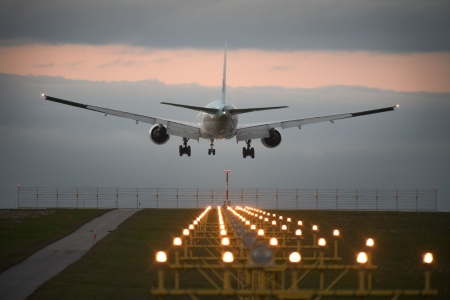 TAKEOFF: Photo of an airplane just before landing. Runway lights can be seen in the foreground.