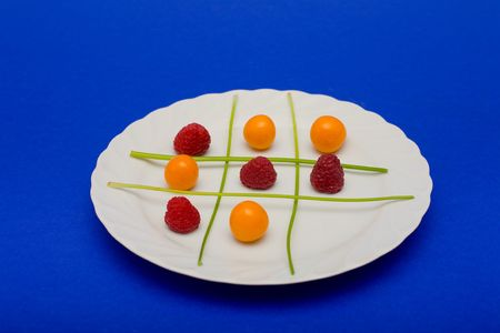 Cape gooseberries, raspberries and parsel arranged on a plate to look like a game of tic tac toe Stock Photo - 2150219