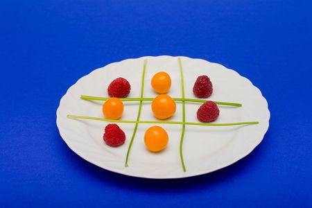 parsel: Cape gooseberries, raspberries and parsel arranged on a plate to look like a game of tic tac toe