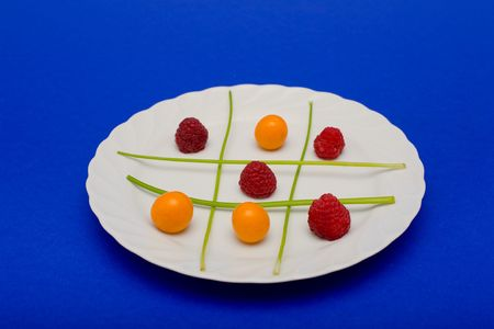 Cape gooseberries, raspberries and parsel arranged on a plate to look like a game of tic tac toe.  Stock Photo