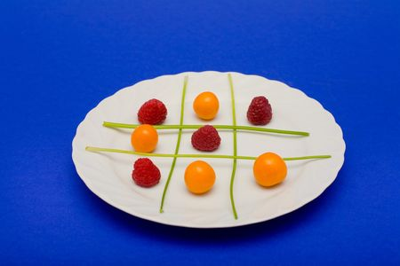 Cape gooseberries, raspberries and parsel arranged on a plate to look like a game of tic tac toe. Stock Photo - 2155125