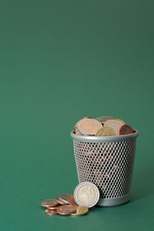 saving tips: Photo of a waste basket full of coins.