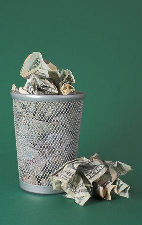 wasteful: Photo of a waste basket full of money.