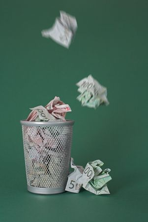 Photo of a waste basket full of money - some bills are just dropped in the basket.