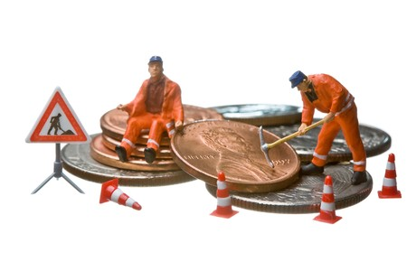 Miniature figures working on a heap of Dollar coins.