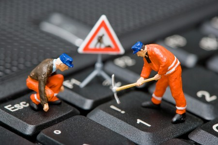 Macro shot of miniature figures working on a computer keyboard.