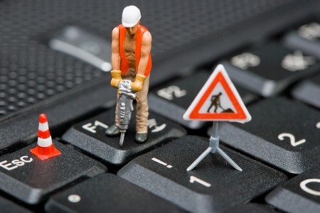 Macro shot of miniature figures working on a computer keyboard.